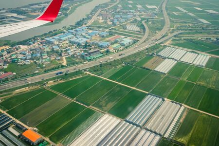 Photo pour Airplane over the green fields. Asia, agricultural area. The wing is visible in the porthole. Muted tones, vignetting. - image libre de droit