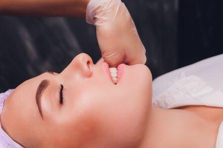 Photo pour cosmetologist makes a buccal massage of the patients facial muscles. - image libre de droit