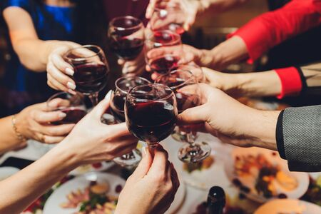 Photo for Close up shot of group of people clinking glasses with wine or champagne in front of bokeh background. older people hands. - Royalty Free Image