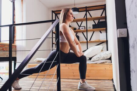 Photo for Attrctive fitness woman doing stretching exercises at home, as part of a healthy lifestyle without going to the gym - Royalty Free Image