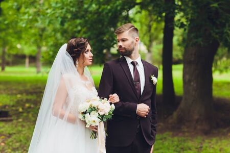 Photo pour happy bride and groom at a park on their wedding day. - image libre de droit