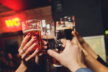 Photo for Close up shot of group of people clinking glasses with wine or champagne in front of bokeh background. older people hands - Royalty Free Image