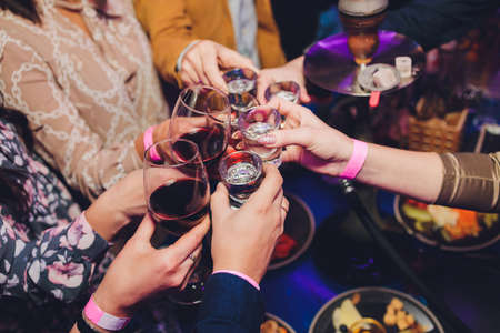 Photo pour Close up shot of group of people clinking glasses with wine or champagne in front of bokeh background. older people hands. - image libre de droit