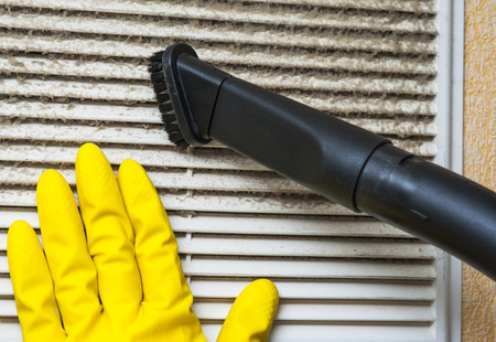 Photo pour Hand in yellow glove and vacuum cleaner pipe. Ventilation grill cleaning. - image libre de droit