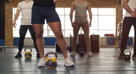 Photo pour Small Group of Muscular Male Adults Lifting Kettlebells. - image libre de droit