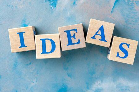 Photo pour Wooden cubes with word IDEAS on blue table. - image libre de droit