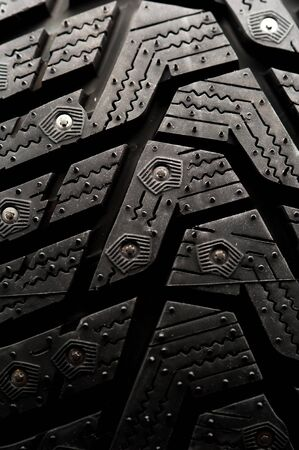 Photo for Close-up studded car tire stands on a black background. Automotive industry concept. The concept of sports equipment in the gym. Place for text - Royalty Free Image