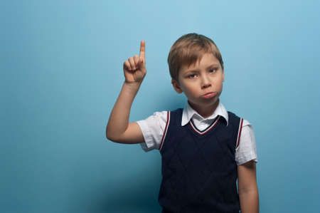 Photo pour Funny Little boy an elementary school student pointing his finger posing on blue background. - image libre de droit