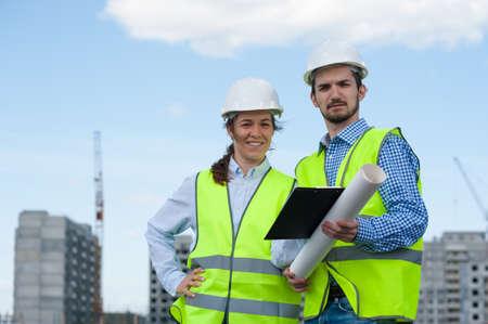 Foto de Two Young Engineers Man and Woman In Green Vests And Helmets - Imagen libre de derechos