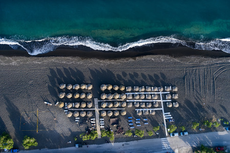 Top view of Perissa beach on the Greek island of Santorini with sunbeds and umbrellas. Beach is covered with fine black sand, and drops off sharply into the water.