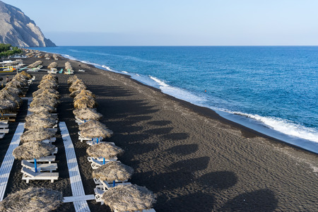 SANTORINI, GREECE - MAY 15,2015: Top view of Perissa beach on the Greek island of Santorini with sunbeds and umbrellas. Beach is covered with fine black sand, and drops off sharply into the water.