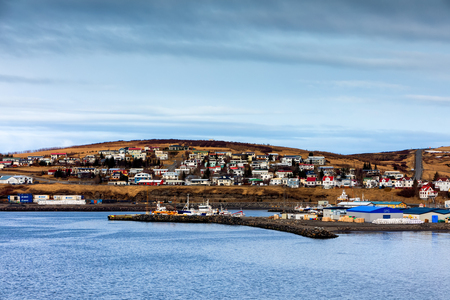 Husavik, Iceland - March 29, 2017: Beautiful view of the historic town of Husavik with traditional houses and traditional fisherman boats lying in the harbor, northern coast of Iceland