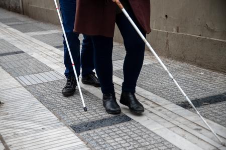 Photo pour blind man and woman walking on the street using a white walking stick - image libre de droit