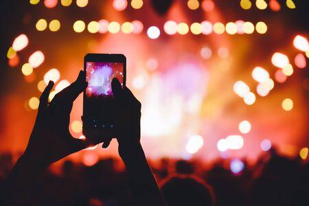 Photo pour People taking photographs with touch smart phone during a music entertainment public concert.  live concert, music festival, happy youth, luxury party, landscape exterior. Selctive Focus - image libre de droit
