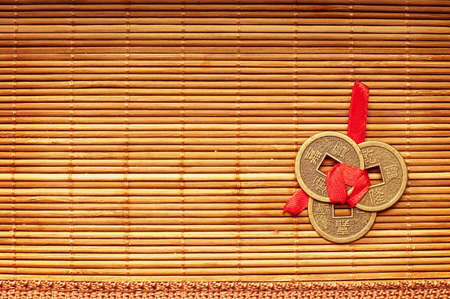 Three Chinese lucky coins tied with red ribbon on wooden mat