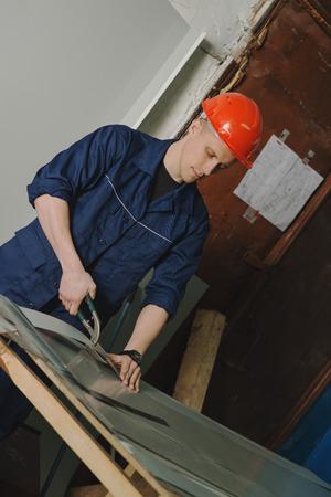 Worker cuts metal sheet with a cutter, closeup