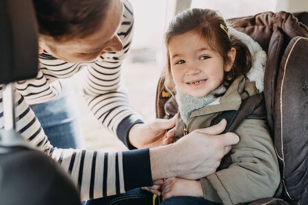 Photo pour father securing his toddler daughter in the coat buckled into her baby car seat - image libre de droit