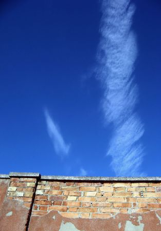 Ancient wall on blue sky with clouds