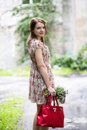 Woman in flowered dress hold flowers and bag