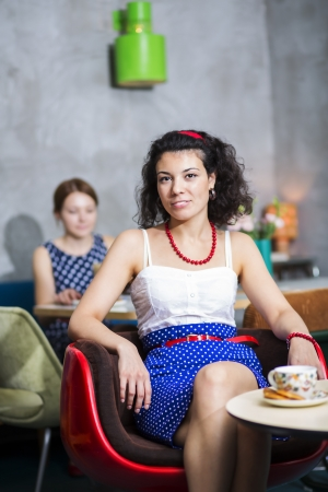 Woman on chair in café with cheerful smile