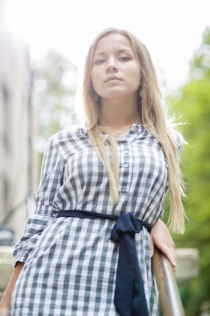 Young woman in checkered dress at bright daylight