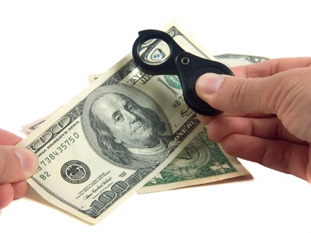 safety checks the dollar banknotes by means of magnifying glasses