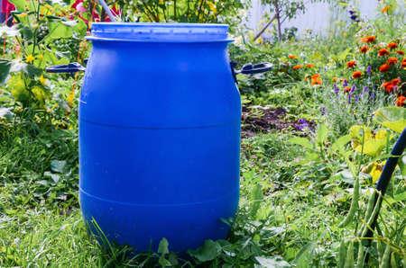 Foto für Large blue plastic garden barrel with handles outdoors in the garden. Rainwater tank in the garden on a sunny summer day. Objects in the garden. - Lizenzfreies Bild