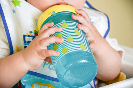 Photo pour One-year-old child holds a spill-proof drinking bowl with two hands. Baby hands close-up. Infant nutrition. - image libre de droit