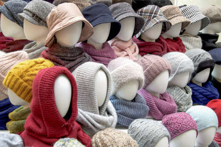 Showcase of trade tent with variety of women's hats for the autumn and winter seasons - knitted hats, scarves, hats. Small and medium-sized clothing business, product demonstration, seasonal sales.