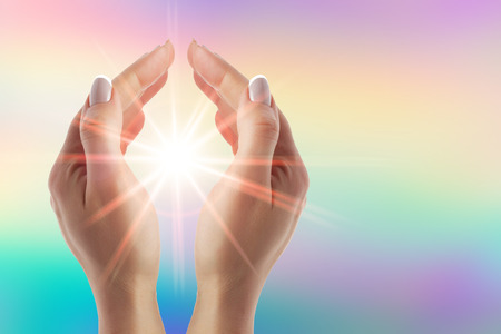 Photo for Healing hands with bright sunburst on rainbow background - Royalty Free Image