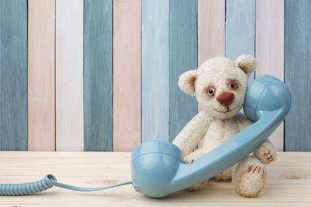 Photo pour Vintage Teddy Bear with retro telephone on wooden background - image libre de droit