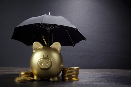 Photo pour Gold Piggy bank with umbrella concept for finance insurance, protection, safe investment or banking - image libre de droit