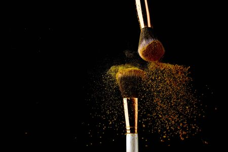 Photo for Cosmetic brush with golden powder spreading on black background - Royalty Free Image