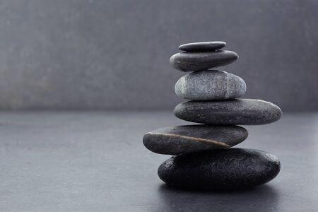 Photo pour zen stones in balanced pile on dark grey background - image libre de droit