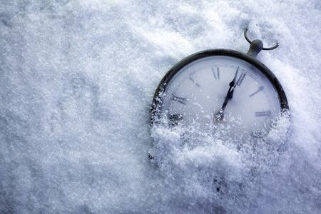 Foto de Christmas Time Clock under white snow, countdown to midnight - Imagen libre de derechos