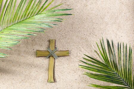 Photo for Cross and Palm Tree Leaves on sand. Palm sunday concept. Top view - Royalty Free Image