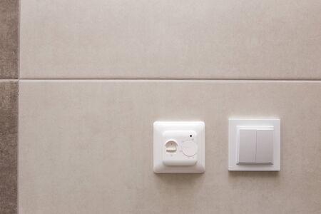 Photo pour White temperature controller of a warm floor on a gray wall. - image libre de droit