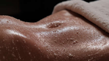 Photo for Cleansing massage for the body. Body scrub for clean skin. Masseur massages the stomach of a girl close-up. - Royalty Free Image