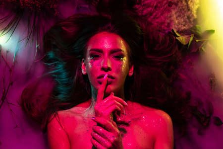 Photo pour Portrait of a girl with glitter on her body in pink creative light. The girl lies in flowers and smoke. - image libre de droit