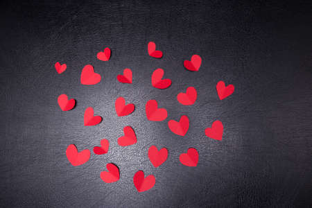 Photo pour A lot of small hearts of red color against on a black background. Happy Valentines Day. - image libre de droit