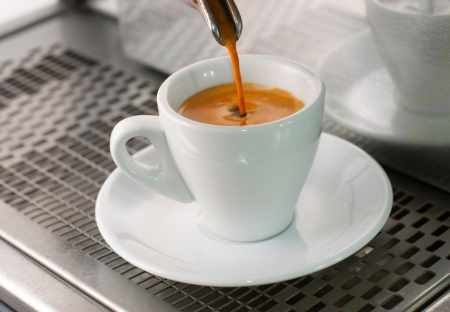 Espresso pours out of a group head into a coffee shot glass.