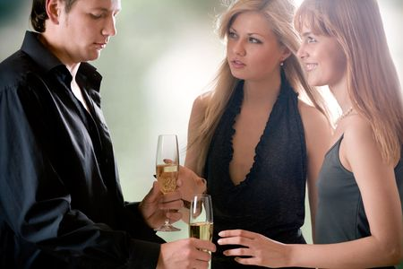Young man with two glasses with champagne and two women standing together, outdoors