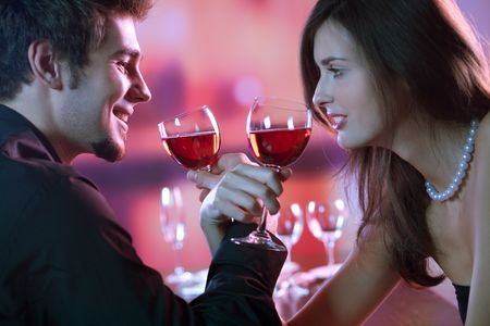 Foto de Young couple sharing a glass of red wine in restaurant, celebrating or on romantic date - Imagen libre de derechos
