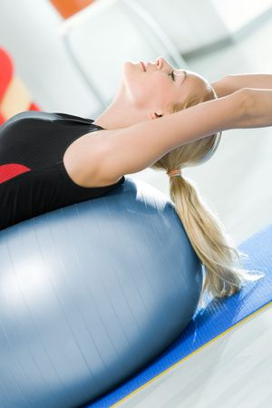 Young happy woman doing exercises with fitball