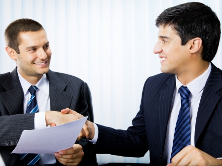 Two businesspeople, or businessman and client, with document handshaking at office