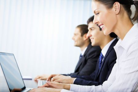 Three young successful businesspeople working at office