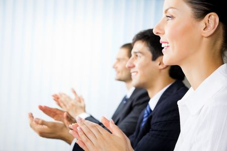 Three happy clapping businesspeople at presentation, meeting, seminar or conference
