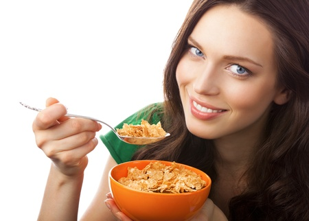 Portrait of young smiling woman eating muesli or cornflakes, isolated on white background