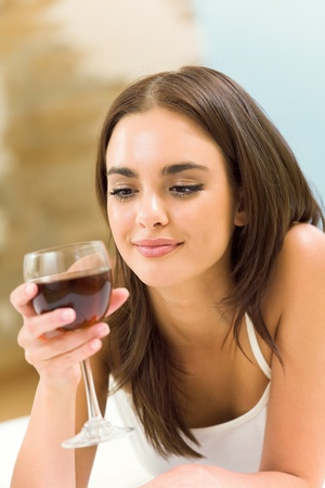 Portrait of young woman with glass of red wine, on bed