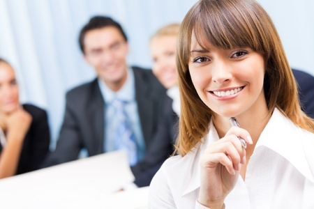Portrait of happy smiling businesswoman and colleagues on background, at office
